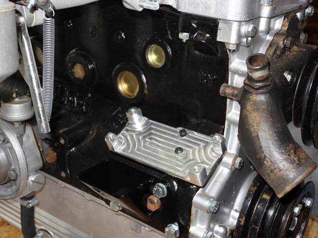 The coil pack mounting bracket locates in the vacated distributor drive hole