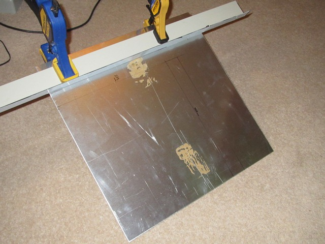 A length of steel angle (actually some shed roof edging) was used to make sure the aluminium plate was cut to size with straight edges